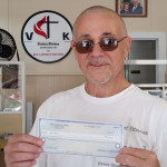 Image of man (Bruce) holding donation check for Victory Kitchen