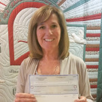 Photo of Marge holding donation check for Stein Hospice Camp Good Grief