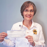 Photo of Sue holding donation check for Serving Our Seniors